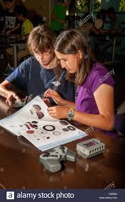 avid teen girls pore over a vex robotics assembly manual at a