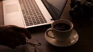 cropped image of a young man working on his laptop in a coffee