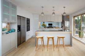 stylish kitchen large windows white cabinets light flooring and caesarstone