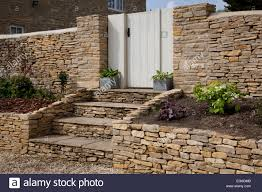 dry stone wall and steps with gateway into english stock photo