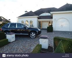 porsche home garage luxury home with porsche cayenne in the driveway stock photo