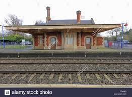 Track Canopy by Looking Across The Tracks At An Old Station Building With A Wooden