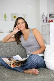 woman sat at home reading magazine on couch stock photo picture