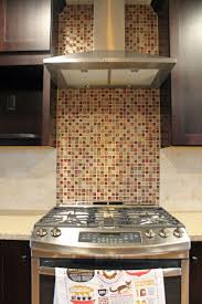 kitchen mosaic tile backsplash with stainless steel vent hood and