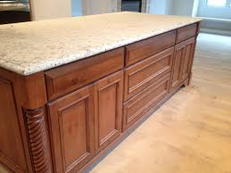 custom warm stained kitchen island with contrasting white granite