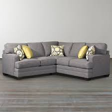small grey l shaped couch with arms and wooden legs for living