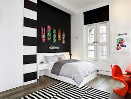 black and white bedroom with corner shelves and green accents