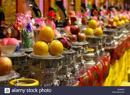 a bowl of fruit on a table with decorations in buddhist temple