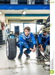 Garage Length by Mechanic Crouching While Changing Car Tire At Garage Stock Photo