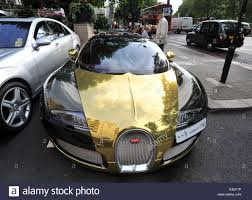 bugatti gold passers by stop to check out two flashy cars parked outside the