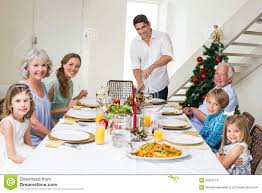 family having christmas meal at dining table stock photo image