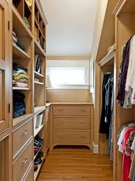narrow walk in closet in loft space with light brown dresser and