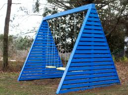 outdoor a swing with a blue color in the yard and then the trees