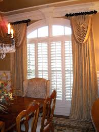 windowtreatments ring curtains with swags in gold silk with gold