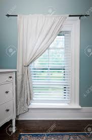 window with venetian blinds and white curtain in country style