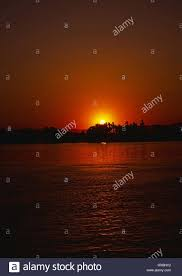 egypt river nile sunset setting sun red orange colours black trees