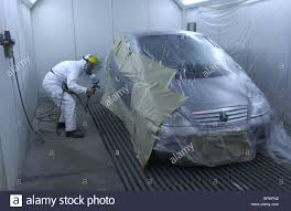 spray paint booth a man in a spray paint booth works on a car repair uk stock photo