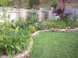 curving paths run beside a large lawn steps rise to shaded garden