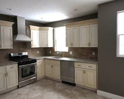 dark gray walls with antique white cabinets and stainless