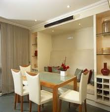 a built in banquette is flanked by tall glass cabinets for storing