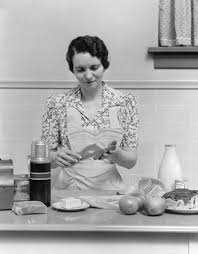 1930s Kitchen 1930s Woman Housewife In Kitchen Wearing Apron Making Sandwich