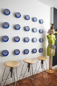 20 caviar cans spaced evenly on a kitchen wall take on an abstract