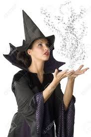 pretty witch with black dress and hat doing a magic spell stock