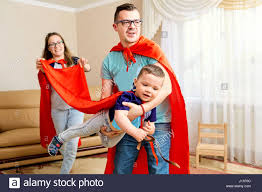 a family dressed in costumes plays the room stock photo