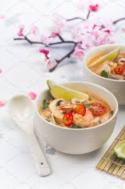 drink table traditional tom yum soup with blooming sakura branch on white