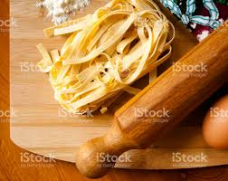 italian tagliatelle on a chopping board together with some