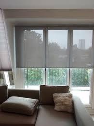 Sun Blocking Window Treatments - sunscreen roller blinds over bi fold doors in living room