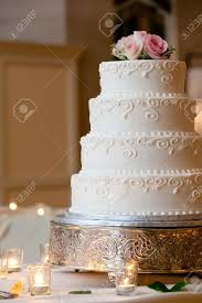 a multi level white wedding cake on a silver base and pink flowers