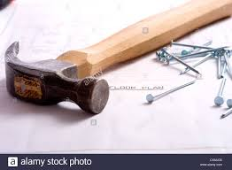 a hammer and nails lying on top of a house floor plan or blue