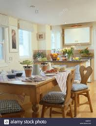 blue checked cushions on old pine chairs at table set for