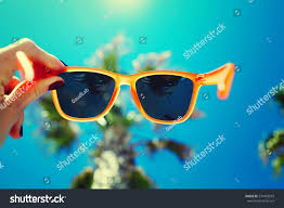 female hand holding colorful sunglasses against stock photo