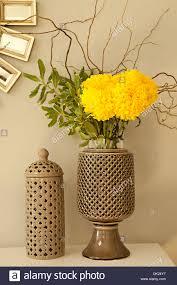 close up of yellow mums flower arrangement in ceramic vase stock