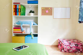 colorful kids room with comfortable bed and white bookcase stock