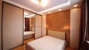 Small Bedroom With Double Bed - small bedroom with closet large mirror and beige double bed stock