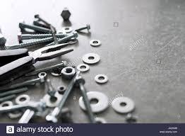 construction tools the screws nuts and bolts with pliers on