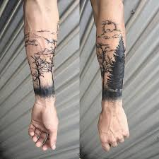 black ink forearm tattoo of forest with man and fire