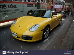 porsche india man driving porsche cayman luxury car through the busy roads in