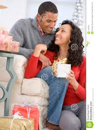 husband and wife exchanging christmas gifts stock photo image