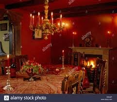Red Dining Room by Lit Red Candles In Chandelier Above Table With Paisley Cloth And