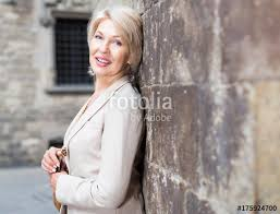 elegant mature woman elegant mature woman is posing near old wall stock photo and