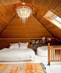 wooden attic bedroom with chandelier and skylight different