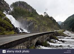 beautiful road and old stone bridge above waterfall in norway