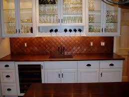 copper kitchen cabinets under cabinet vent hood mozaic copper backsplash white kitchen