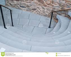 unique stairs with curved concrete steps near stone wall stock