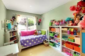 kids bedroom with green walls and purple bed and may toys stock