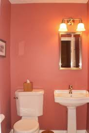 pink color of small bathroom ideas with wall light above mirror